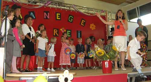 buntgeschmückten Bühne und werden von der Schulleiterin begrüßt